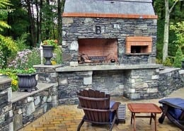 A massive outdoor fireplace, pizza oven and a steak fry. Custom pillars, walls, firewood storage. Textured concrete caps and hearth. A true piece of art!